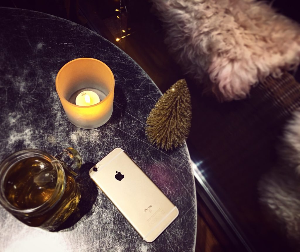 Warm mood with Christmas tea and the candle light and a gold iPhone